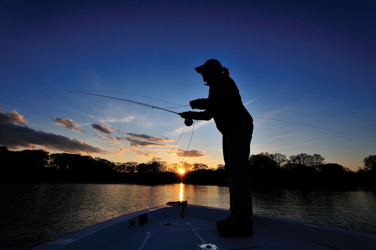 Stripers slurp spawning worms as the sun sets over a Rhode Island salt pond, where Capt. Bob Hines is guiding a client. Photographer Barry Beck caught the action.