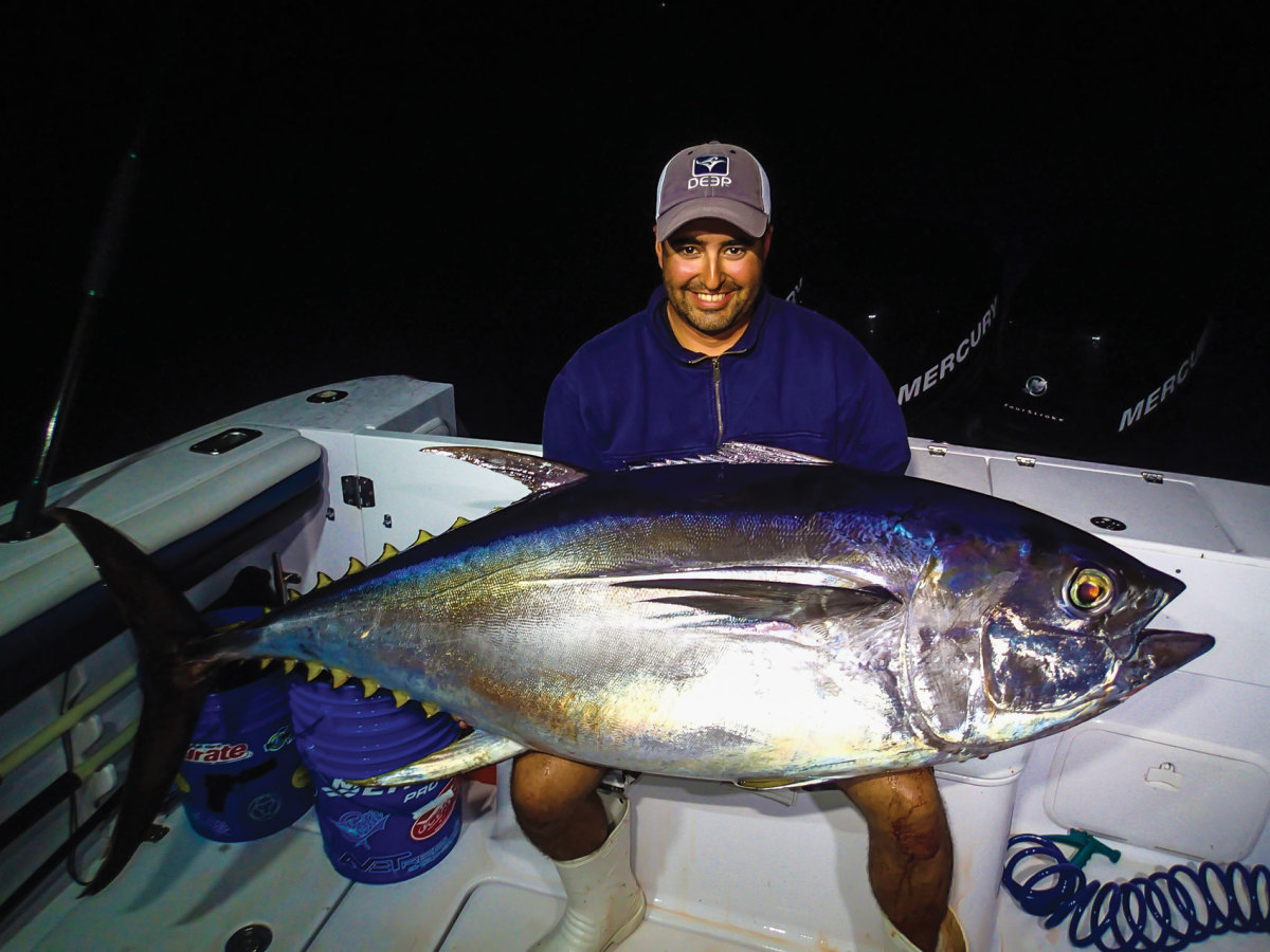 R.I. charter captain Louis J. DeFusco cradles a 210-pound bigeye taken on 60-pound fluorocarbon and spinning gear