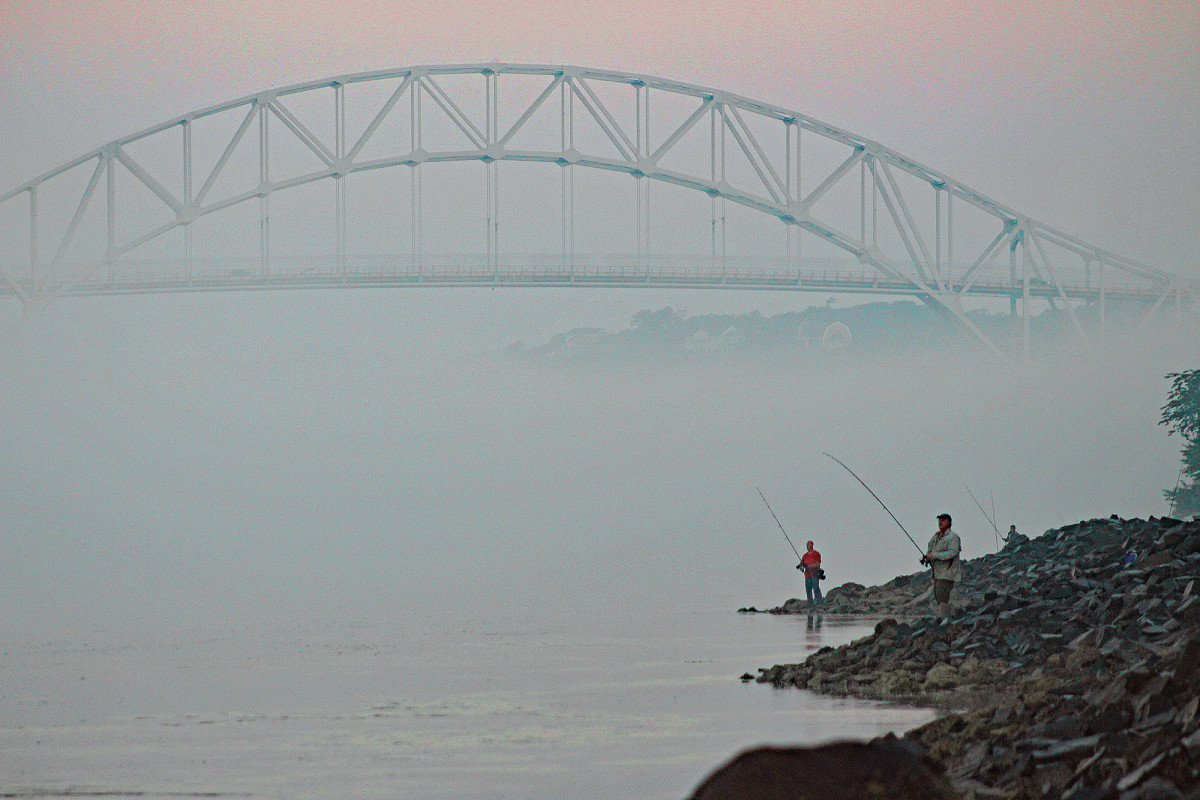 A couple of canal sharpies work the current near the Sagamore Bridge on a foggy day.