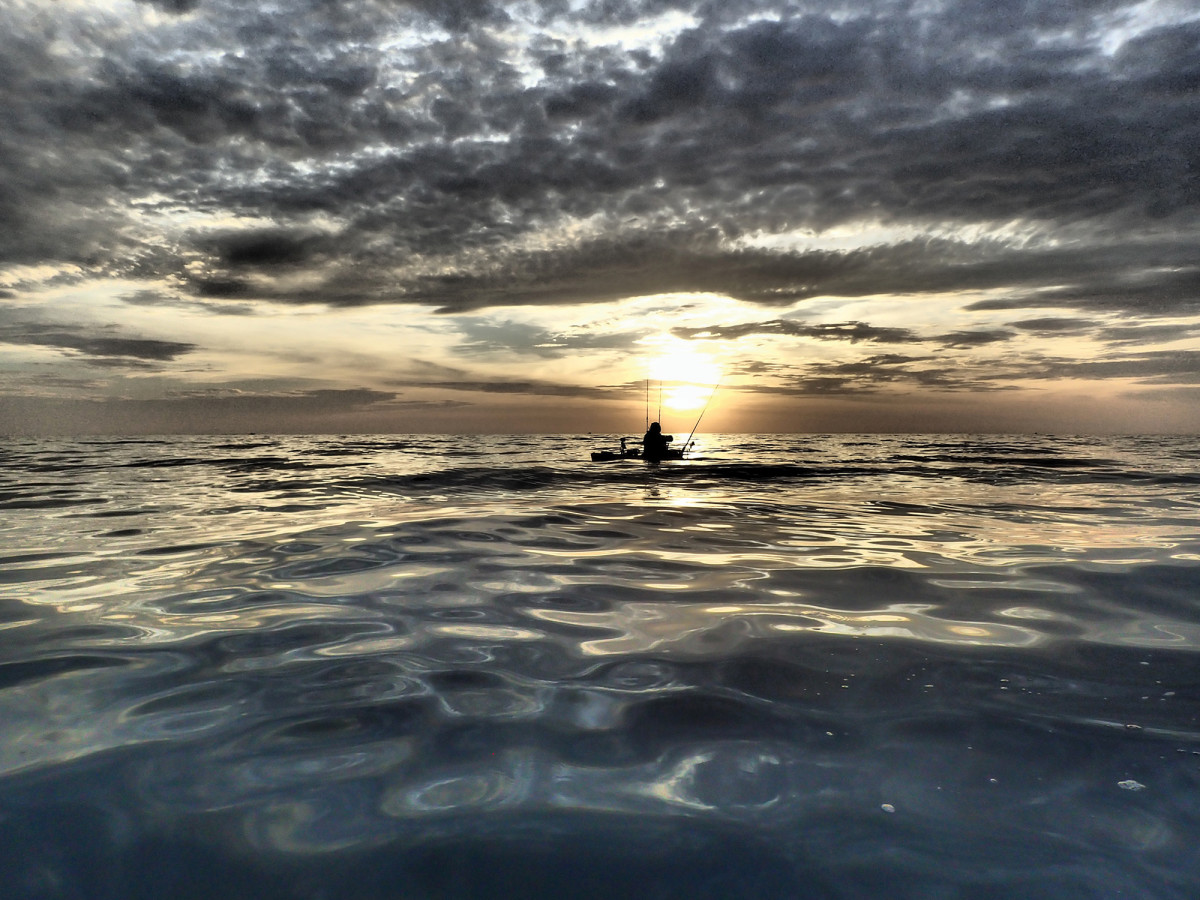 "A kayak angler moves in silence off Baja as the panga ""mothership"" departs."