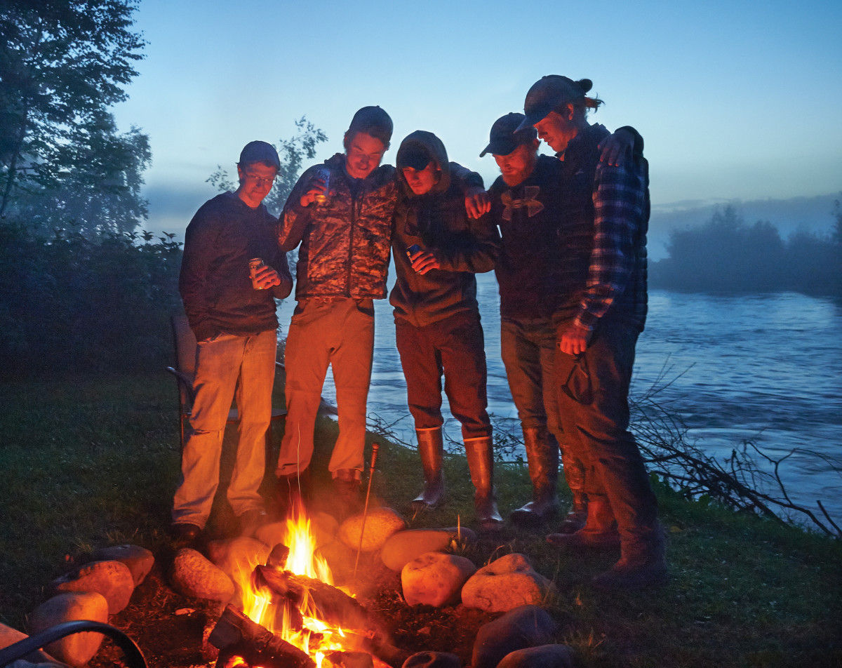At 9 p.m. in the land of the midnight sun, guides and employees of Riversong Lodge gather around the fire.