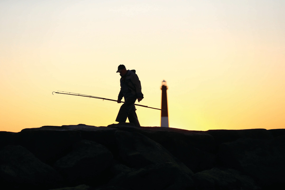 Long-handled gaff in hand, a surfman walks out on the north jetty at Barnegat Inlet, New Jersey.