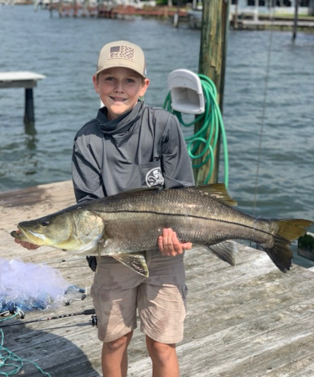 A big snook caught off a small, canal-side dock.