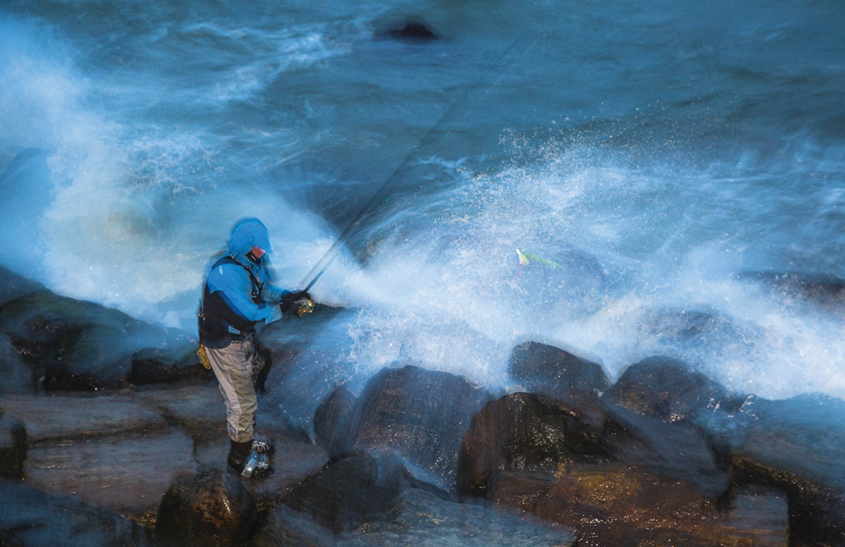 An angler loads up one of the few casts left in the season among surf and structure.