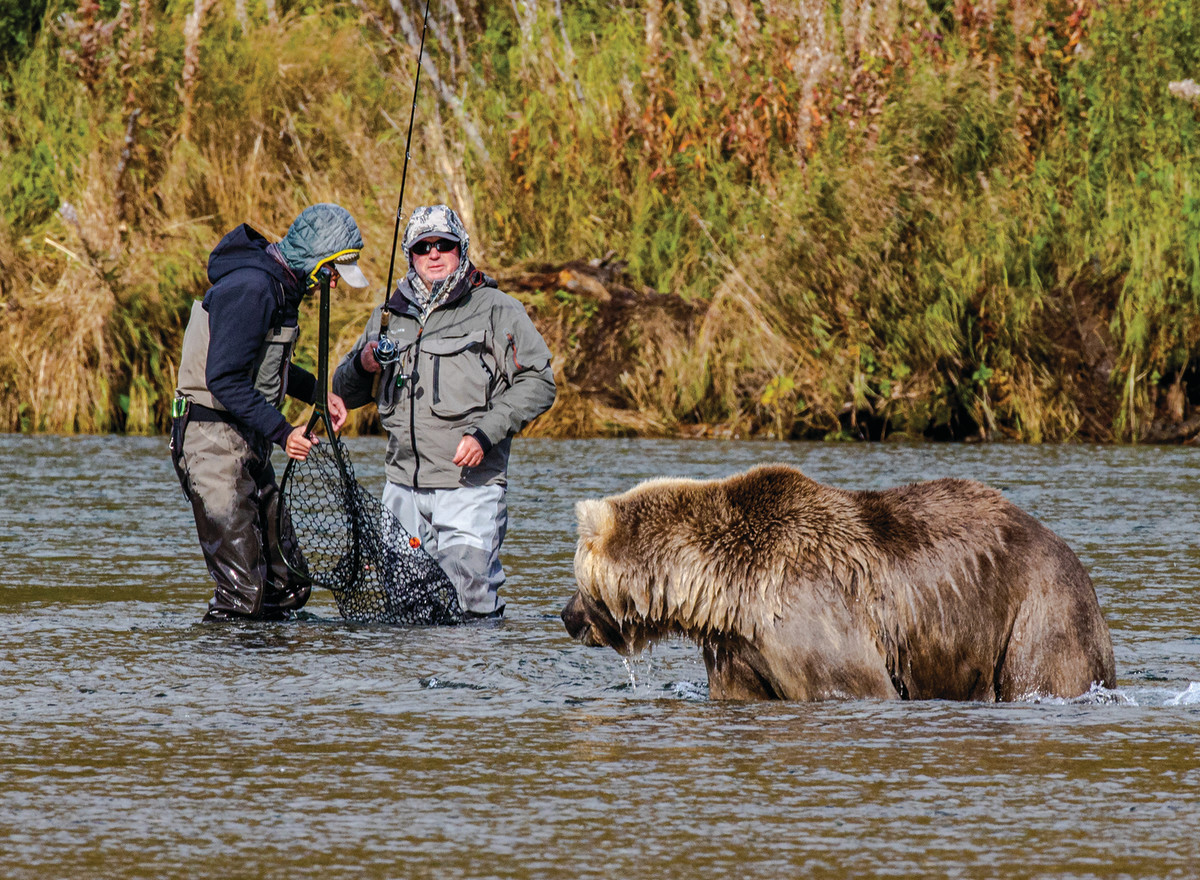 A pair of anglers and a bear eye each other up.