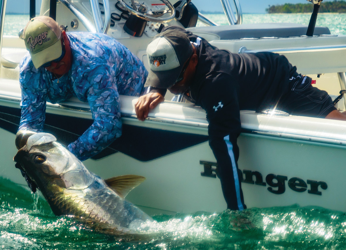 Green (right) and Capt. Curt Romanowski of Florida Backwater Charters tangle with a tarpon.